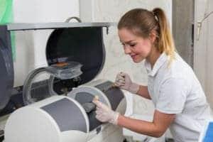 Dental assistant operates CEREC machine